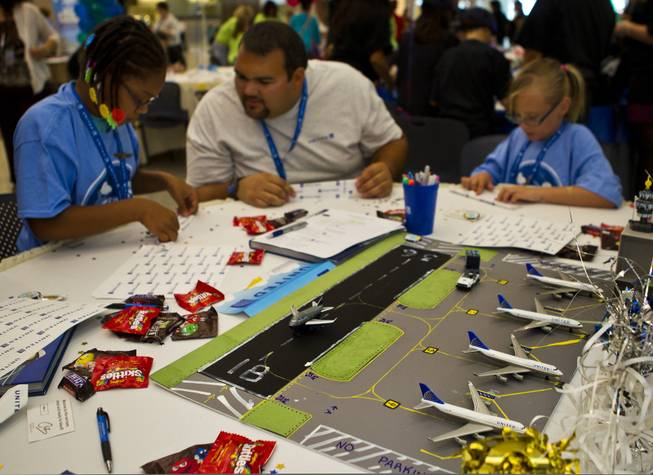 The United Airlines team members fold their airplanes before the Paper Plane Palooza competition begins at McCarran International Airport on Tuesday, August 12, 2014.