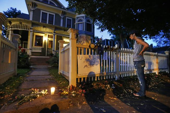 Angie Campbell stops to pay respects at a makeshift memorial outside the home where the 80s TV series Mork & Mindy, starring the late Robin Williams, was set, in Boulder, Colo., Monday Aug. 11, 2014. Robin Williams, the Academy Award winner and comic supernova whose explosions of pop culture riffs and impressions dazzled audiences for decades died Monday in an apparent suicide. He was 63.