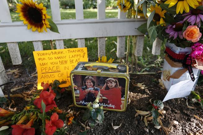 Flowers, notes, and a Mork & Mindy commemorative lunchbox are among the things left at a makeshift memorial in Boulder, Colo., Tuesday Aug. 12, 2014, outside the home where the 80s TV series Mork & Mindy, starring the late Robin Williams, was set. Williams, the Academy Award winner and comic supernova whose explosions of pop culture riffs and impressions dazzled audiences for decades and made him a gleamy-eyed laureate for the Information Age, died Monday, Aug. 11, in an apparent suicide. He was 63.