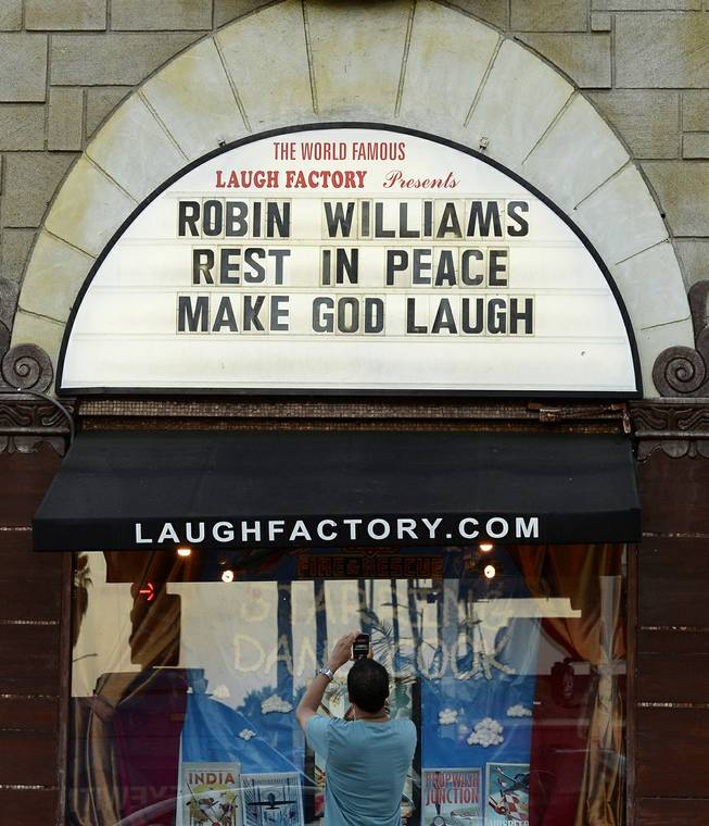 A man takes a photo of a the marquee of the Laugh Factory with a message in memory of actor Robin Williams displayed, in the Hollywood district of Los Angeles Monday, Aug. 11, 2014. Williams, the Academy Award winner and comic supernova whose explosions of pop culture riffs and impressions dazzled audiences for decades died Monday in an apparent suicide at his San Francisco Bay area home. He was 63.