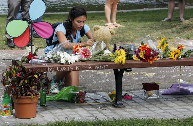 "Mariagrazia LaFauci, 24, of Waltham, Mass. places a teddy bear on a bench at Boston's Public Garden, Tuesday, Aug. 12, 2014, where a small memorial has sprung up at the place where Robin Williams filmed a scene during the movie, ""Good Will Hunting."" Williams, 63, died at his San Francisco Bay Area home Monday in an apparent suicide."