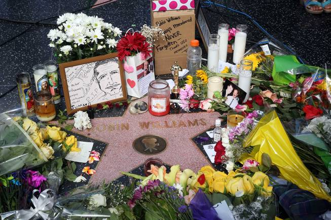 Flowers, photographs and candles surround the star of actor-comedian Robin Williams along the Hollywood Walk of Fame in Los Angeles on Tuesday, Aug. 12, 2014. Williams, 63, died at his San Francisco Bay Area home Monday in an apparent suicide.