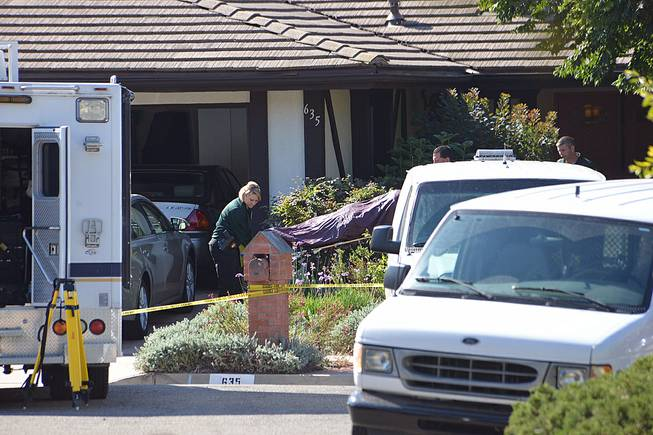 Investigators remove a body from a home in Goleta, Calif., Tuesday, Aug. 12, 2014, where four people and a dog were found stabbed to death the night before. Authorities said the sole suspect, a 46-year-old man, was arrested without incident Tuesday.