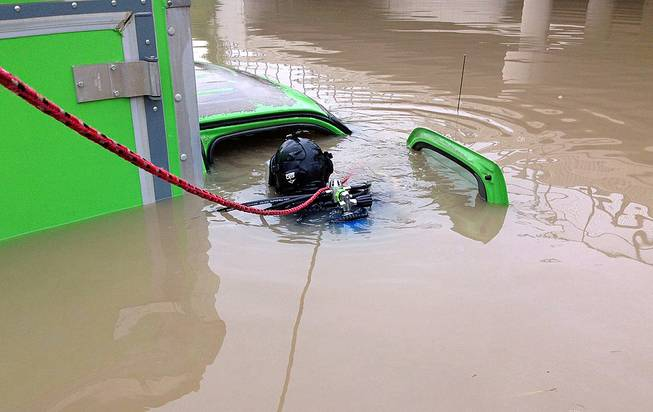 In a photo provided by the Michigan State Police, a diver with the department's Underwater Recovery Unit inspects a vehicle, Tuesday, Aug. 12, 2014, submerged on a Detroit area freeway a day after heavy of rain.