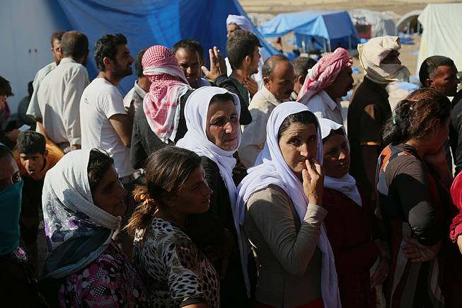 Displaced Iraqis from the Yazidi community gather for humanitarian aid at Nowruz camp, in Derike, Syria, Tuesday, Aug. 12, 2014. In the camps here, Iraqi refugees have new heroes: Syrian Kurdish fighters who battled militants to carve an escape route to tens of thousands trapped on a mountaintop.