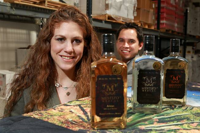 Jessica Rosman and Arturo Palencia of Skere Spirits are seen with the three different mezcals their company produces Friday, Aug. 8, 2014.