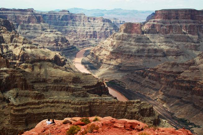 A couple takes in the view of the Colorado River as it runs through the Grand Canyon at Grand Canyon West Tuesday, Aug. 12, 2014.