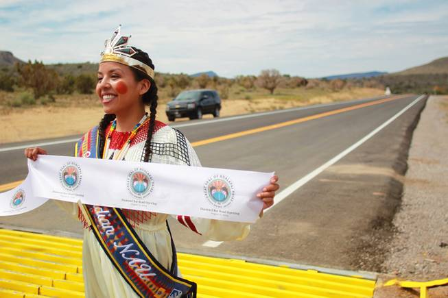 Jewel Diamond Honga holds one end of a ribbon during the official opening of the newly paved section of Diamond Bar Road leading to Grand Canyon West Tuesday, Tuesday, Aug. 12, 2014.