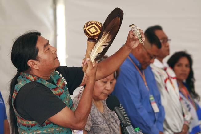 Frank Mapatis performs a traditional Hualapai prayer during the official opening of the newly paved section of Diamond Bar Road leading to Grand Canyon West Tuesday, Tuesday, Aug. 12, 2014.