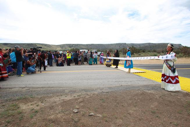 A ribbon is prepared to be cut during the official opening of the newly paved section of Diamond Bar Road leading to Grand Canyon West Tuesday, Tuesday, Aug. 12, 2014.