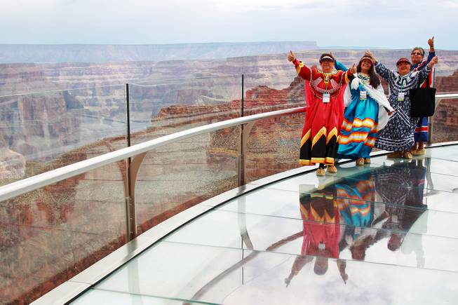 Hualapai tribe members pose for a photo on the Skywalk after the official opening of the newly paved section of Diamond Bar Road leading to Grand Canyon West Tuesday, Tuesday, Aug. 12, 2014.