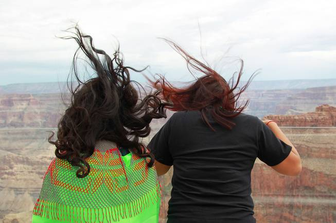 The hair of Joyce Paya, left, and Deshay Benson is blow up from a breeze on the Skywalk after the official opening of the newly paved section of Diamond Bar Road leading to Grand Canyon West Tuesday, Tuesday, Aug. 12, 2014.