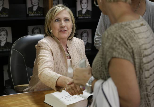 "Former Secretary of State Hillary Rodham Clinton shakes hands with a customer at Bunch of Grapes Bookstore, in Vineyard Haven, Mass., on the island of Martha's Vineyard, Wednesday, Aug. 13, 2014, during a book signing event for her memoir ""Hard Choices.""  Clinton says she's looking forward to hugging out her differences with President Barack Obama. Obama's former secretary of state told reporters Wednesday that she's proud to have served with him despite some differences of opinion."