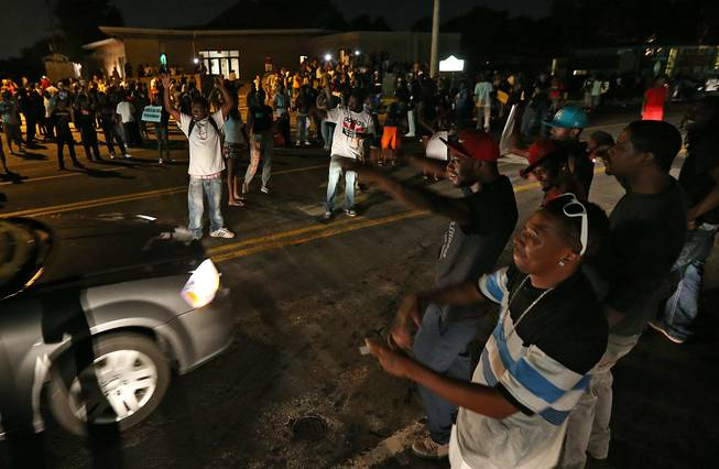A group demonstrates along and in the middle of Chambers Road outside the Greater St. Mark Missionary Baptist Church after the conclusion of a gathering with Michael Brown's family and Rev. Al Sharpton on Tuesday, Aug. 12, 2014, in Dellwood. The gathering at the church was in response to the police shooting of 18-year-old Michael Brown on Saturday.