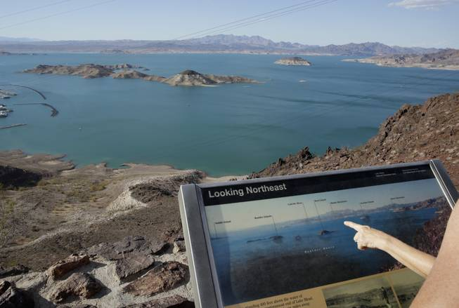 In this July 24, 2014, photo, dropping water levels reveal larger islands in Lake Mead compared to a picture on an interpretive sign on a hill overlooking the lake in Lake Mead National Recreation Area.