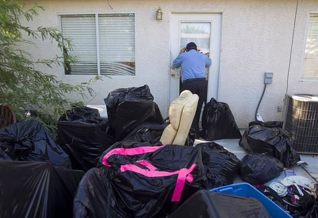 North Las Vegas Animal Control officer Dale Smock looks into the back door of a home in North Las Vegas Thursday Aug. 14, 2014. Smock recently helped clear a house of over 100 cats. The house has since been condemned.