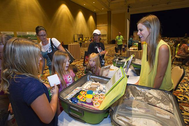 Mckenzie Peterson, right, of Desert Research Institute's GreenPower, talks with children of teachers during MGM Resorts annual Educator Appreciation Day at the Mirage Thursday Aug. 14, 2014.