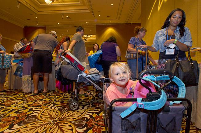 Eleanor Stender, 5, sits in a wagon as her mother, an art teacher at Fremont Middle School, gathers school supplies during MGM Resorts annual Educator Appreciation Day at the Mirage Thursday Aug. 14, 2014. In addition to school supplies provided by MGM Resort employees, a variety of agencies participated in the days activities to introduce educators to teaching resources available in the community.