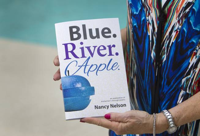 "Nancy Nelson, 70, holds her book of poetry titled ""Blue. River. Apple."" at her home in Summerlin on Tuesday, Aug. 12, 2014. After being diagnosed with early-onset Alzheimer's disease last year, Nelson began waking up at 3 a.m. and would write poetry, she said."