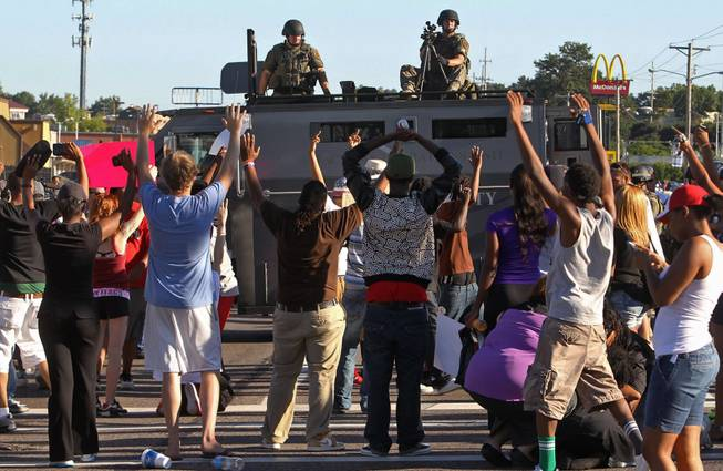 Protesters raise their hands in front of police atop an armored vehicle in Ferguson, Mo. on Wednesday, Aug. 13, 2014. On Saturday, Aug. 9, 2014, a white police officer fatally shot Michael Brown, an unarmed black teenager, in the St. Louis suburb.