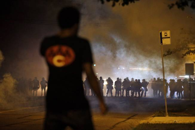 A man watches as police walk through a cloud of smoke during a clash with protesters Wednesday, Aug. 13, 2014, in Ferguson, Mo. Protests in the St. Louis suburb rocked by racial unrest since a white police officer shot an unarmed black teenager to death turned violent Wednesday night, with people lobbing Molotov cocktails at police who responded with smoke bombs and tear gas to disperse the crowd.