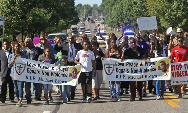 A march organized by area ministers makes its way down W. Florissant in Ferguson, Mo. on Wednesday, Aug. 13, 2014. On Saturday, Aug. 9, 2014, a white police officer fatally shot Michael Brown, an unarmed black teenager, in the St. Louis suburb.
