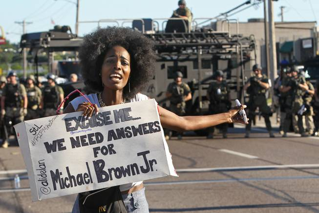 A protester shouts as she moves away from a line of riot police in Ferguson, Mo. on Wednesday, Aug. 13, 2014. On Saturday, Aug. 9, 2014, a white police officer fatally shot Michael Brown, an unarmed black teenager, in the St. Louis suburb.