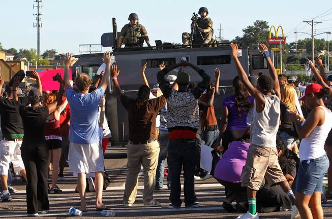 Protesters raise their hands in front of police atop an armored vehicle in Ferguson, Mo. on Wednesday, Aug. 13, 2014. On Saturday, Aug. 9, 2014, a police officer fatally shot Michael Brown, an unarmed black teenager, in the St. Louis suburb.