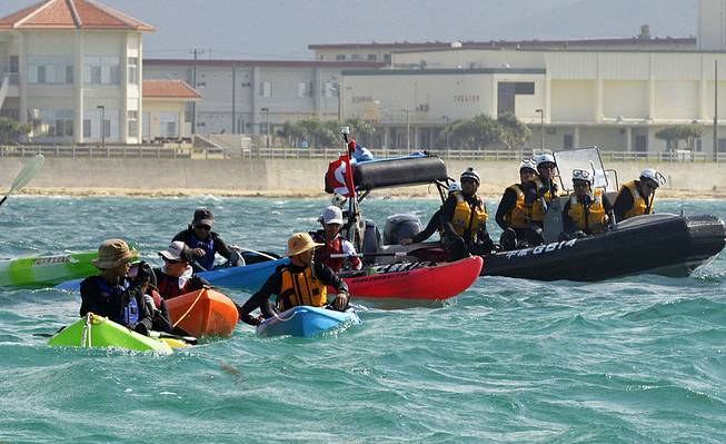 Anti-U.S. base protesters in canoe are blocked by a Japan Coast Guard speed boat in Nago, Okinawa, southern Japan, Thursday, Aug. 14, 2014. Japanese officials said buoys are being floated off the southernmost island of Okinawa in one of the first steps in the relocation of an American military base.
