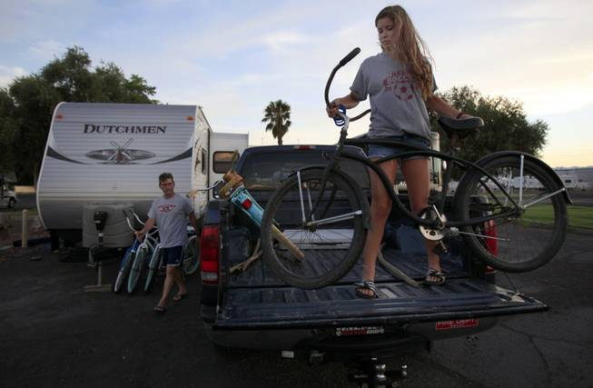 Modesto, Calif., residents Carlos, left, and Isabela Meza unload their bikes as they set up camp for the night at the KOA campground on the Strip. In late September, the camp will lose its lease with Circus Circus, which has other development plans that have sent KOA officials looking for a new site.