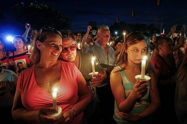 Sharon Kestner, left, enjoys the sounds of Elvis, as Brian Bush rests his head on her shoulder outside the gates of Graceland during a candlelight vigil in remembrance of Elvis' death 37 years-ago, Friday, Aug. 15, 2014, in Memphis, Tenn. Kestner and Bush are from Lexington, Ky.