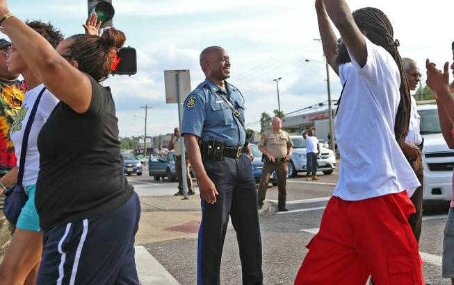 Capt. Ronald Johnson of the Missouri Highway Patrol smiles at demonstrators march along West Florissant Avenue in Ferguson, Mo., on Thursday, Aug. 14, 2014. The Missouri Highway Patrol took control of a St. Louis suburb Thursday, stripping local police of their law-enforcement authority after four days of clashes between officers in riot gear and furious crowds protesting the death of an unarmed black teen shot by an officer.