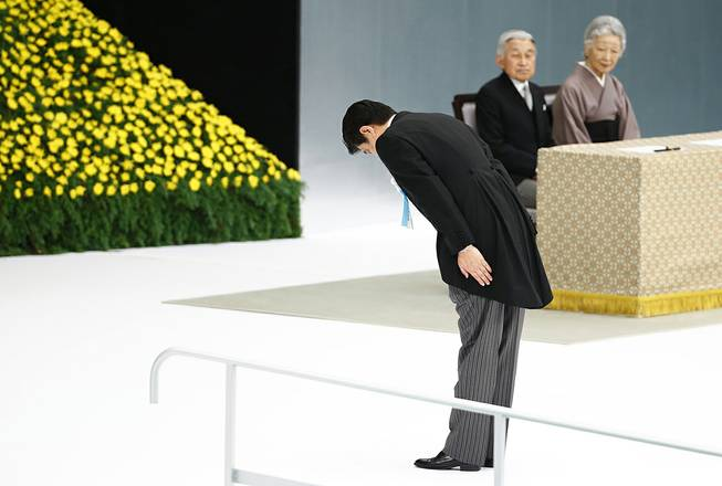 Japanese Prime Minister Shinzo Abe bows before the main altar decorated with huge bank of chrysanthemums as he offers prayers for the war dead during a memorial ceremony at Budokan Martial Arts Hall in Tokyo, Friday, Aug. 15, 2014. Abe visited Yasukuni in December 2013, drawing widespread criticism. But Aug. 15 is a key date as it marks the day in 1945, when Emperor Hirohito announced the surrender on the radio. Japan on Friday, marked the 69th anniversary of its surrender, ending the WWII.