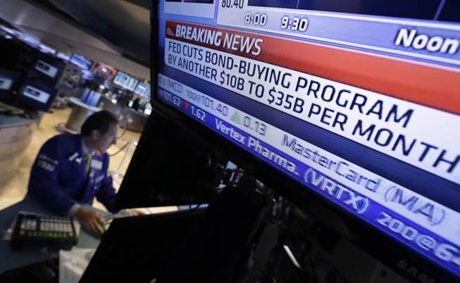In this June 18, 2014, file photo, a television monitor at a trading post on the floor of the New York Stock Exchange shows the decision of the Federal Reserve.