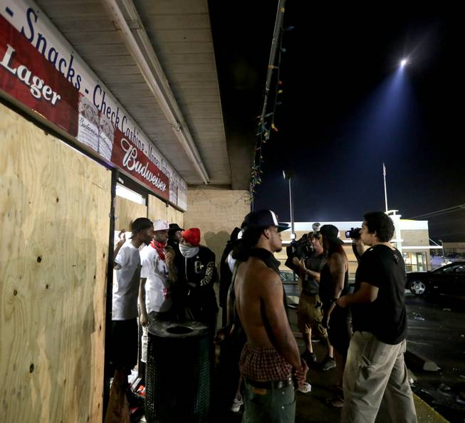 People stand in front of a convenience store after it was looted early Saturday, Aug. 16, 2014, in Ferguson, Mo. The violence stemmed from the shooting death of Michael Brown by police a week ago after the teen allegedly stole  a box of cigars from the store.