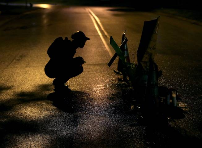 Ty Crustfield pauses, Friday, Aug. 15, 2014, before a makeshift memorial in the middle of the street where Michael Brown was killed by police nearly a week ago in Ferguson, Mo.