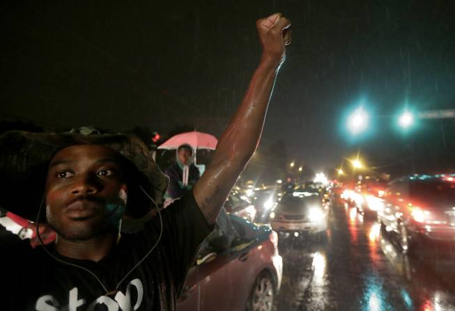 A protester holds up a clenched fist Friday, Aug. 15, 2014, in front of a convenience store that was looted and burned following the shooting death of Michael Brown by police nearly a week ago in Ferguson, Mo.  A suburban St. Louis police chief on Friday identified the officer whose fatal shooting ignited days of heated protests, and released documents alleging the teen was killed after a robbery in which he was suspected of stealing a box of cigars.