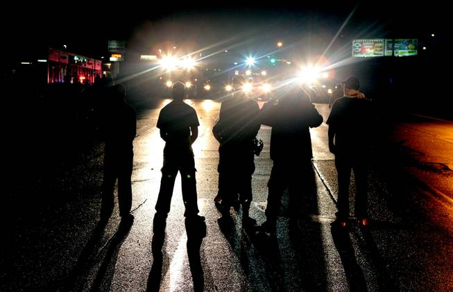 Against a backdrop of flood lights from police tactical vehicles, protestors stand their ground in the middle of West Florissant Avenue in Ferguson, refusing to leave despite police orders early Saturday, Aug. 16, 2014.