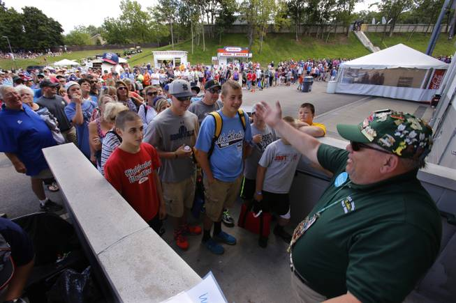 Lamade Stadium usher Dave Stoker, right, opens the gates for a crowd gathered to see a baseball game between Chicago and Las Vegas in United States pool play at the Little League World Series tournament in South Williamsport, Pa., Sunday, Aug. 17, 2014.