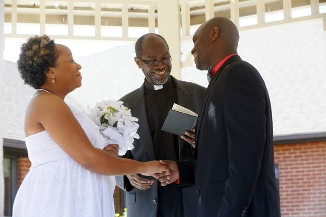 Pastor Robert Davis, the father of the groom, center, conducts the marriage ceremony between Miriam Reeves, left, and Mark Davis beneath the gazebo in the courtyard of Foundation Park Alzheimer's Care on Saturday, Aug. 16, 2014.