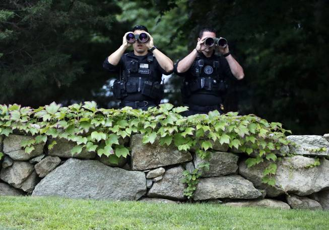 Two law enforcement officials use binoculars near the entrance to State Road Restaurant, Saturday, Aug. 16, 2014, in West Tisbury, Mass., moments before the arrival of President Barack Obama and first lady Michelle Obama for dinner with friends. President Obama is staying on Martha's Vineyard for what is expected to be a two-week summer vacation. (AP Photo/)