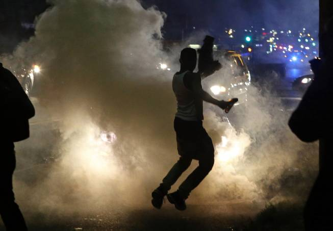 Protesters run when the police shoot tear gas in Ferguson, Mo., Sunday, Aug. 17, 2014. Protests over the killing of 18-year-old Michael Brown by a white police officer have entered their second week.