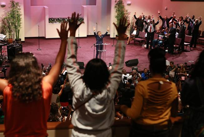 The Rev. Al Sharpton raises his hands with the crowd during a service for the Michael Brown family at the Greater Grace Church in Ferguson, Mo. on Sunday, Aug. 17, 2014. On Saturday, Aug. 9, 2014, a white police officer fatally shot Brown, an unarmed black teenager, in the St. Louis suburb.