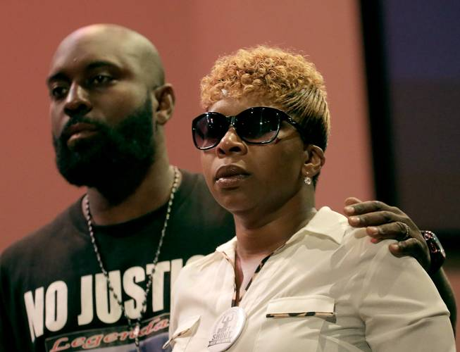 Parents of Michael Brown, Michael Brown Sr. and Lesley McSpadden, listen to a speaker during a rally, Sunday, Aug. 17, 2014, for their son who was killed by police last Saturday in Ferguson, Mo.