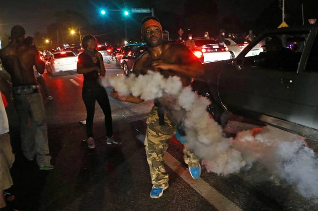 A protester tries to throw tear gas back at the police in Ferguson, Mo., Sunday, Aug. 17, 2014. Protests over the killing of 18-year-old Michael Brown by a white police officer have entered their second week.