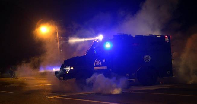 A tactical trucks moves down the street through tear gas in Ferguson, Mo., Sunday, Aug. 17, 2014. Protests over the killing of 18-year-old Michael Brown by a white police officer have entered their second week.