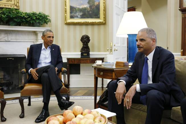 President Barack Obama speaks with Attorney General Eric Holder as news photographers photograph their meeting regarding the fatal police shooting of a black teenager in Ferguson, Missouri, Monday, Aug. 18, 2014, in the Oval Office of the White House in Washington.