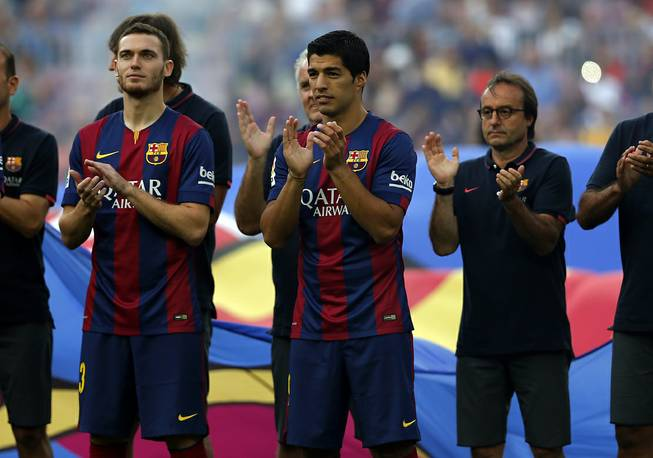 Barcelona's Luis Suarez, from Uruguay, center, reacts during the official presentation of the Barcelona F.C. team for the season 2014-15 ahead of the Joan Gamper trophy match at the Camp Nou in Barcelona, Spain, Monday, Aug. 18, 2014.