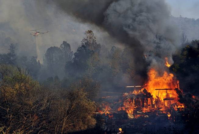 A structure burns along Highway 41 in Oakhurst, Calif., Monday, Aug. 18, 2014. One of several wildfires burning across California prompted the evacuation of hundreds of people in a central California foothill community near Yosemite National Park, authorities said.
