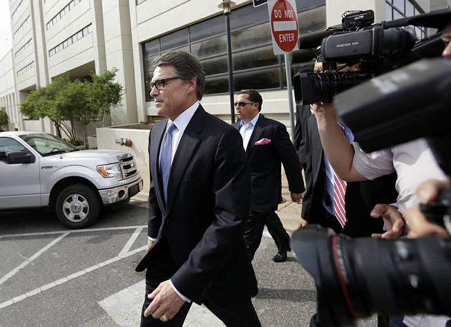 Texas Gov. Rick Perry, left, leaves the Blackwell Thurman Criminal Justice Center after he was booked, Tuesday, Aug. 19, 2014, in Austin, Texas. Perry was indicted last week on charges of coercion and official oppression for publicly promising to veto $7.5 million for the state public integrity unit run.